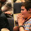 "Globe/Roger Nomer<br /> Isaac Dickinson, a seventh grader at Thomas Jefferson, listens intently to Marion Blumenthal Lazan's presentation while holding her book ""Four Perfect Pebbles"" on Tuesday."