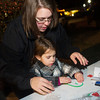 "Globe/Roger Nomer<br /> Justine Bell, Webb City, helps her daughter Sophia, 3, with a candy cane ornament during a kids activity at the ""Holiday Tree Lighting"" at Spiva Park on Monday evening."