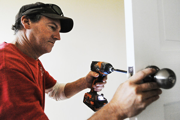 Joe Jamerson, American Construction foreman, installs an interior door knob Tuesday morning, Nov. 5, 2013, at the future Loving Grace House, 1414 Euclid, in Joplin.<br /> Globe | T. Rob Brown