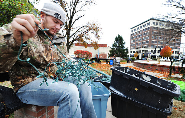 Seasonal city of Joplin employee Jarred English helps separate holiday lights and check to make sure they still work Wednesday afternoon, Nov. 20, 2013, in Spvia Park, downtown Joplin.<br /> Globe | T. Rob Brown