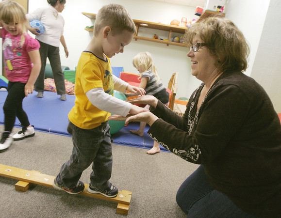 Globe/Roger Nomer<br /> Christy Graham, executive director at Cerebral Palsy of Tri-County, helps Braxden Carey, 3, on a balance beam on Wednesday.