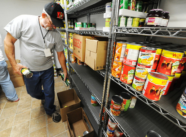Ted Londo, pantry manager, adds cans to boxes for clients Friday, Nov. 8, 2013, at Soul's Harbor in Joplin.<br /> Globe | T. Rob Brown
