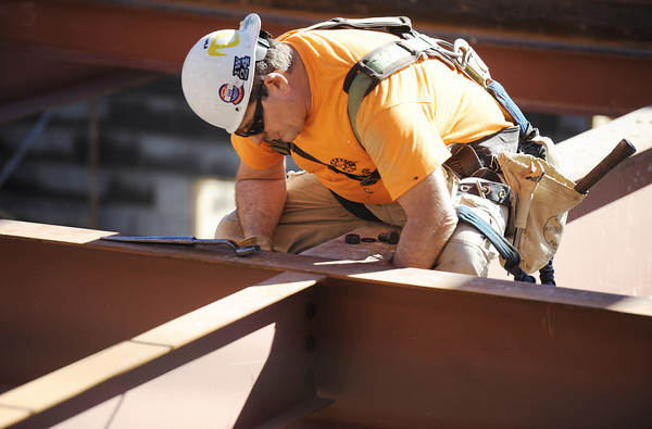 Jack Daugherty, a journeyman iron worker Local 584 with Weaver Steel of St. Louis, installs bolts on large steel I-beams Thursday afternoon, Nov. 7, 2013, during construction of the new Joplin High School.<br /> Globe | T. Rob Brown