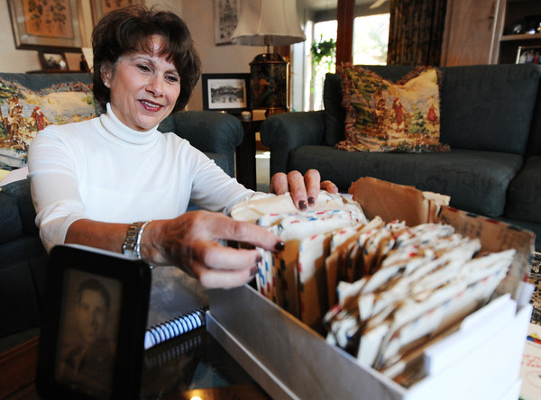 Nancy Harrison looks through a box of about 150 handwritten letters her father wrote to her mother during World War II.<br /> Globe | T. Rob Brown