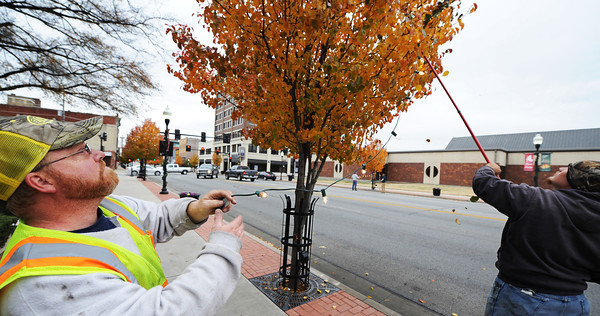 City of Joplin employees Gary Hatfield (left), signing & traffic technician, and Tyler Ebbs, street department laborer, put up seasonal lights in trees Wednesday afternoon, Nov. 20, 2013, along Main Street in downtown Joplin.<br /> Globe | T. Rob Brown