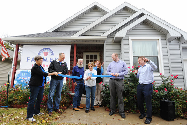 Homeowner Ron and Margaret (center) cut the ribbon Tuesday afternoon, Nov. 5, 2013, outside their remodeled home. It was the 100th home done through Rebuild Joplin.<br /> Globe | T. Rob Brown