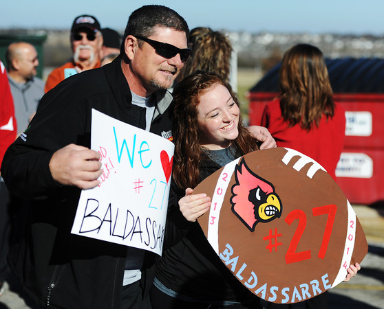 Kyle Baldassarre's father Paul Baldassarre and Kyle's sister Lexy Baldassarre hold up signs in support of the Webb City football player as family and fans greet the players Thursday afternoon, Nov. 28, 2013, outside Webb City High School just before the team left for St. Louis to compete in the Missouri State Championship football game Friday.<br /> Globe | T. Rob Brown