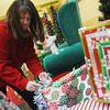 Globe/Roger Nomer<br /> Kim King, property accounts manager, ties a bow on present at the Santa set at Northpark Mall on Tuesday.
