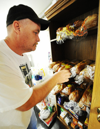 Brian Branham, pantry employee, arranges loaves of bread Friday, Nov. 8, 2013, at Soul's Harbor in Joplin.<br /> Globe | T. Rob Brown