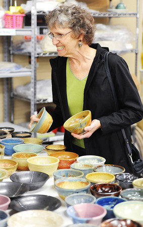 Patron Eunice LeRoy of rural Joplin smiles as she tries to make a selection from the plethora of Empty Bowls Thursday afternoon, Nov. 21, 2013, during the charity event at Phoenix Fired Art on South Main Street, Joplin.<br /> Globe | T. Rob Brown