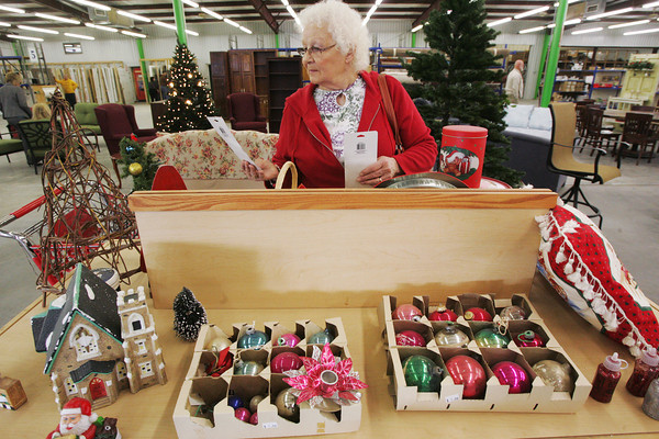 Globe/Roger Nomer<br /> Helen Kropp, Carterville, looks through a selection of Christmas decorations during the grand opening of the Joplin Area Habitat for Humanity Restore at its new location on North Main Street on Tuesday morning.