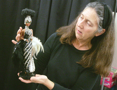 Globe/Roger Nomer Toni LoPresti works with her Starlight Splendor Barbie doll, one of the Bob Mackie designed dolls in her collection.