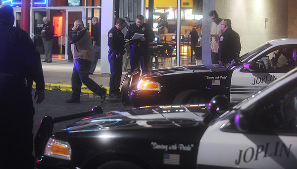 Globe/Roger Nomer<br /> Joplin police investigate the scene of a shooting outside the Regal Northstar Theater on Friday night.  Police say the shooting was targeted and that one male was transported to an area hospital.