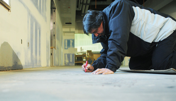 Globe/Roger Nomer<br /> David Fleischman signs the library floor at Soaring Heights Elementary on Tuesday afternoon.  Fleischman has a daughter in first grade who will attend the school when it opens early next year.