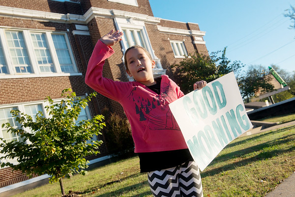 Globe/Roger Nomer<br /> Patience Heinlein, a fifth grader at West Central Elementary, waves at cars on Wednesday morning on Seventh Street outside the school.