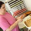 Globe/Roger Nomer<br /> Carrie Pendergraft frosts donuts on Thursday at Dude's Daylight Donuts.