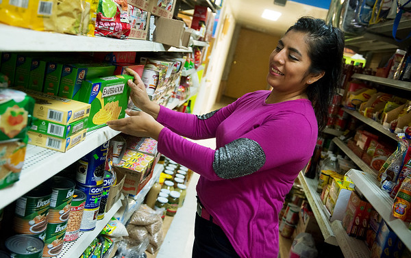 Globe/Roger Nomer<br /> Mildred Guzman arranges an aisle at El Quetzal Restaurant and Bakery on Thursday in Carthage.