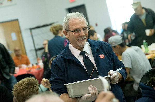 Globe/Roger Nomer<br /> Salvation Army Major Douglas Stearns serves cranberry sauce on Thursday at the Joplin Salvation Army.