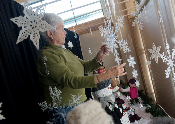 Globe/Roger Nomer<br /> June Stokes arranges snowflakes on Monday in the window of City Hall.