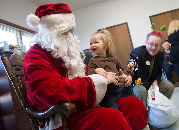 Globe/Roger Nomer<br /> Santa gets an assist from Mark VonMoss, incoming president of the  National Association of Insurance and Financial Advisors-Southwest Missouri, as he holds Nevaeh Armstrong, 3, at the Cerebral Palsy of Tri-County Webb City Development Center on Tuesday morning. In addition to providing the Christmas party and gifts for students at the center, the National Association of Insurance and Financial Advisors-Southwest Missouri gave a check for $3,500 from the NAIFA-SW Help the Children fund, a community service project started over 30 years ago.