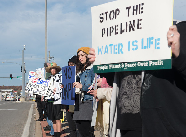 Globe/Roger Nomer<br /> Protesters hold signs asking US Bank to withdraw funding for the Dakota Access Pipeline on Monday in front of US Bank on Range Line.