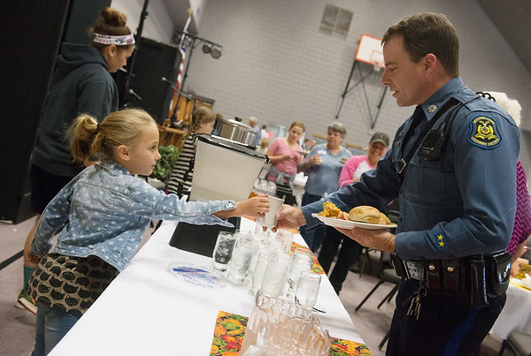 Globe/Roger Nomer<br /> Sawyer Carey, 8, serves coffee to Missouri Highway Patrol Trooper Sam Carpenter on Thursday at First United Methodist Church.