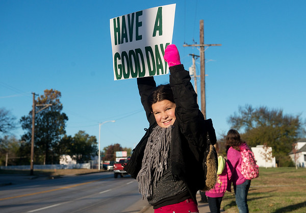 Globe/Roger Nomer<br /> Bailey Gillen, a fourth grader at West Central Elementary, greets drivers on Wednesday morning on Seventh Street outside the school.