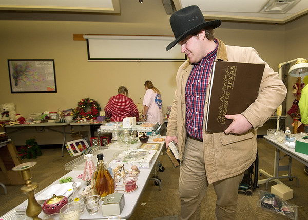 Evan Moore checks out the offerings at the Wildcat Glades Conservation and Audubon Center benefit rummage sale on Friday at the center.<br /> Globe | Laurie Sisk