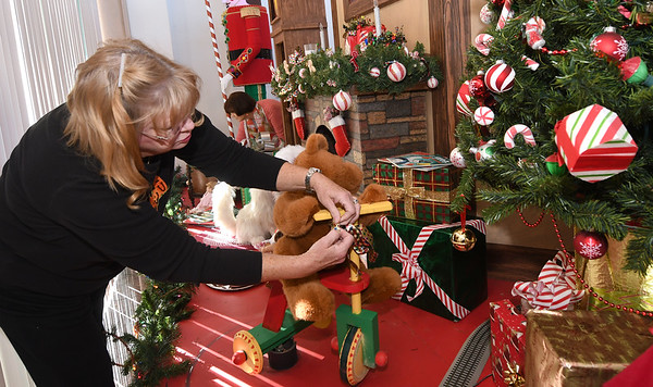 Mary Anne Phillips, of the City of Joplin Window Decorating Committee, puts some finishing touches on the committee's window in preparation for unveiling ceremonies on Monday.<br /> Globe | Laurie Sisk