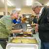 From the left: Gayle O'Hare serves her homemade ham and bean with barley soup to Jim Dawson during the Sixth Annual Empty Bowls benefit on Thursday at Phoenix Fired Art.  Wednesday at about noon, organizers celebrated reaching the $100,000 mark in money raised over the past six years to feed area people in need through various organizations. <br /> Globe | Laurie Sisk