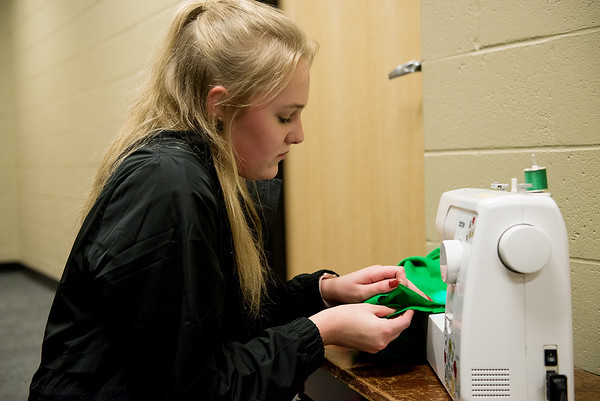 "Globe/Roger Nomer<br /> Isabella St. Clair, sophomore, sews costumes before a rehearsal of ""Crazy Cocoa Christmas"" at Joplin High School on Thursday."