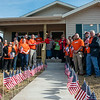 Globe/Roger Nomer<br /> Volunteers and veterans line up for the ribbon cutting for Ronald and Charlotte King's new Habitat for Humanity home on Friday.