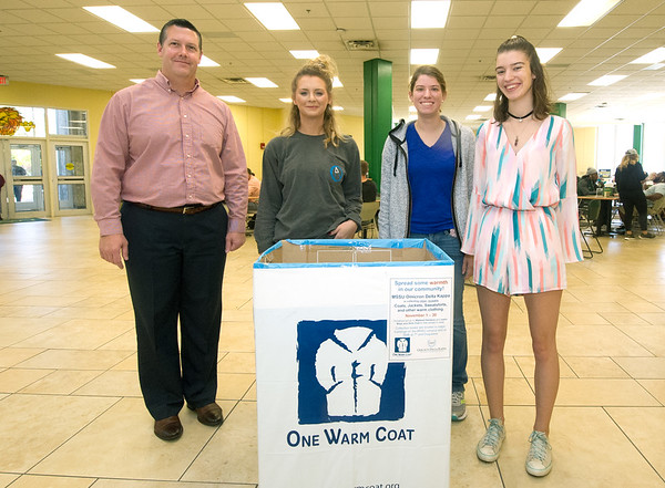 "From the left Omicron Delta Kappa advisor Brian Nichols, ODK Secretary Phaze Roeder, ODK President Kaitlin Fraser and ODK Vice President Grace Scheidemantle stand behind one of 15 collection boxes for the organization's ""One Warm Coat"" drive on Thursday at Missouri Southern's Billingsley Student Center. Collection boxes were placed inside buildings on campus and off-campus at Victory Life Center and two Southwest Missouri Bank locations. The drive continues through the end of the month with a goal of more than 350 articles of warm clothing to be distributed to Watered Gardens and the Boys and Girls Club of Southwest Missouri .<br /> Globe 