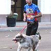 Henri Coeme and his running partner, Miles, both of Neosho, makes their way to the finish line during the Joplin Turkey Trot 5k race in downtown Joplin on Thanksgiving morning. Coeme said he and Miles have logged thousands of race miles together in several states.<br /> Globe | Laurie Sisk