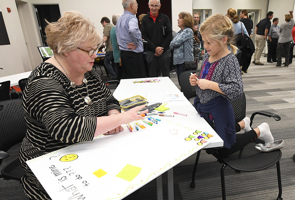 "Seven-year-old Pearl Gaines assigns a ""to-do"" for herself - saving Wildcat Glades rabbit ""Trevor"" -  as Ann Leach looks on during a community informational and brainstorming event to determine the future of Wildcat Glades on Tuesday night at the Joplin Public Library.<br /> Globe 