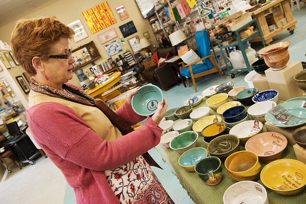 Globe/Roger Nomer<br /> Heather Grills talks about some bowls made by local artist Mark Strayer for the annual Empty Bowls fundraiser at the pottery studio on Friday.