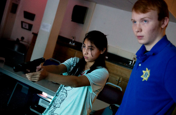 Globe/Roger Nomer<br /> Theodore Sanford, a Crowder senior from Seneca, observes Yvette Mendoza's performance in the shooting simulator on Wednesday at Crowder in Neosho.