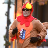 Dressed in full turkey regala, Donnie Gray makes his way to the finish line of the 5k race during the Joplin Turkey Trot in downtown Joplin on Thanksgiving morning.<br /> Globe | Laurie Sisk