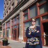 Lori Haun, president of the Downtown Joplin Alliance, stands in front of the Frisco Station on Tuesday. Once a candidate for demolition, the building now serves as low income housing for local residents.<br /> Globe | Laurie Sisk