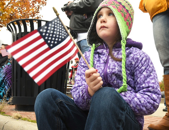 Five-year-old Zoe Devaughn clutches an American flag as entries make their way down Main Street during the Veterans Day Parade on Saturday in downtown Jolin.<br /> Globe | Laurie Sisk