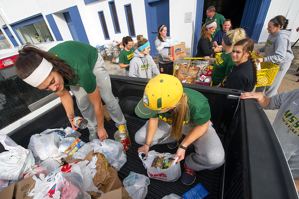 "Missouri Southern softball players Kylie Westbrook, left and Abi Corbett join their teammates on Wednesday at Souls Harbor as they unload about 6,300 food items collected by MSSU athletes during their ""Trick or Treat So Others Can Eat"" food drive. Athletes solicited donations from residences and collected the donations on Monday in preparation for delivery on Wednesday. It is estimated the donations will feed Souls Harbor clients for more than a month.<br /> Globe 
