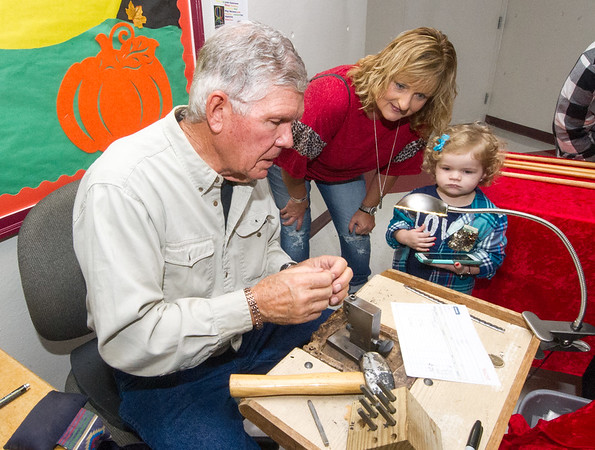 Grove craftsman Tom Thompson crafts a custon ring for Tylee Hobbs, 3, of Pittsburg as her grandmother Robin Glover, also of Pittsburg, looks on during the 27th Annual Cecil Floyd Craft Show on Saturday at the school.<br /> Globe | Laurie Sisk