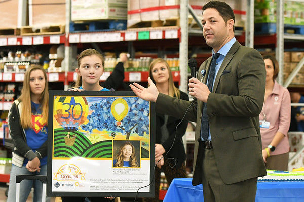 Local artist and Children's Miracle Network Ambassador Yszabehl Sauffer, 15, of Neosho displays the art she created for the Sam's Club CMN six-week fundraising campaign as Freeman Health Systems Developmental Officer Blake Bard speaks during a celebration of the store raising an estimated $70,000 toward the campaign. The amount is the highest of any Sam's Club nationally and will enable Freeman to acheive its goal of placing Angel Eyes monitors over each bed in the hospital's natal intensive care unit. The total raised also represents about half of the money raised by 20 Sam's Clubs and Walmarts in the area.<br /> Globe | Laurie Sisk
