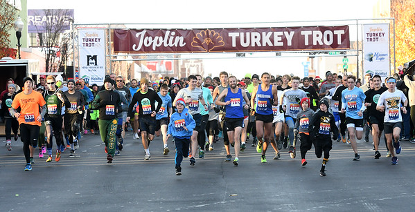 Some of the 1,700 runners participating in the Joplin Turkey Trot begin their 5k race in downtown Joplin on Thanksgiving morning.<br /> Globe | Laurie Sisk