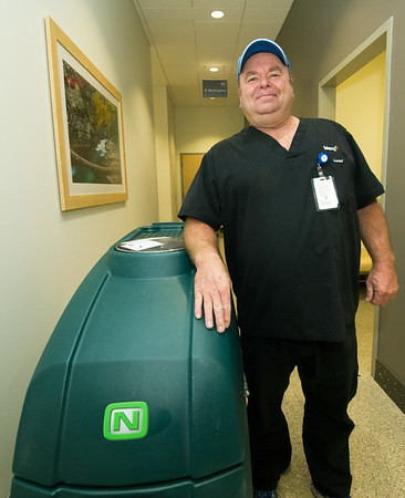 Mercy custodian Brett Caywood stands beside a large machine used to clean floors at the hospital on Thursday morning. Caywood, a Watered Gardens success story, was recently named Employee of the Month in his department.<br /> Globe | Laurie Sisk