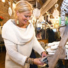 Blue Moon Boutique owner Branden Clark organizes scarves, gloves and hats on Wednesday in her downtown shop in preparation for Small Business Saturday.<br /> Globe | Laurie Sisk