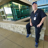 Mercy custodian Brett Caywood takes a break outside the hospital's main entrance on Thursday morning. Caywood, a Watered Gardens success story, was recently named Employee of the Month in his department.<br /> Globe | Laurie Sisk