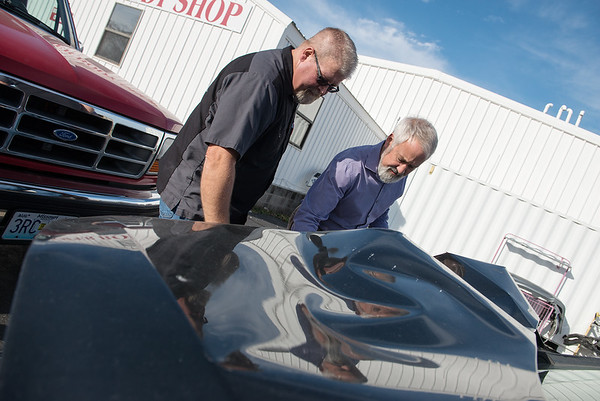 Globe/Roger Nomer<br /> Bubba Conrow, in-house appraiser, left, and Kelly Peterson, body shop manager, look at the crumpled hood of a Kia damaged by a deer on Monday at Roper Body Shop.