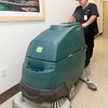 Mercy custodian Brett Caywood uses a large machine to clean a hallway at the hospital on Thursday morning. Caywood, a Watered Gardens success story, was recently named Employee of the Month in his department.<br /> Globe | Laurie Sisk