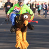 Freeman Health System's Lori Thompson makes her way to the finish line in the 5k race during the Joplin Turkey Trot in downtown Joplin on Thanksgiving morning. Thompson pledged to dress in full turkey attire if 20 of her coworkers joined her in the annual race.<br /> Globe | Laurie Sisk